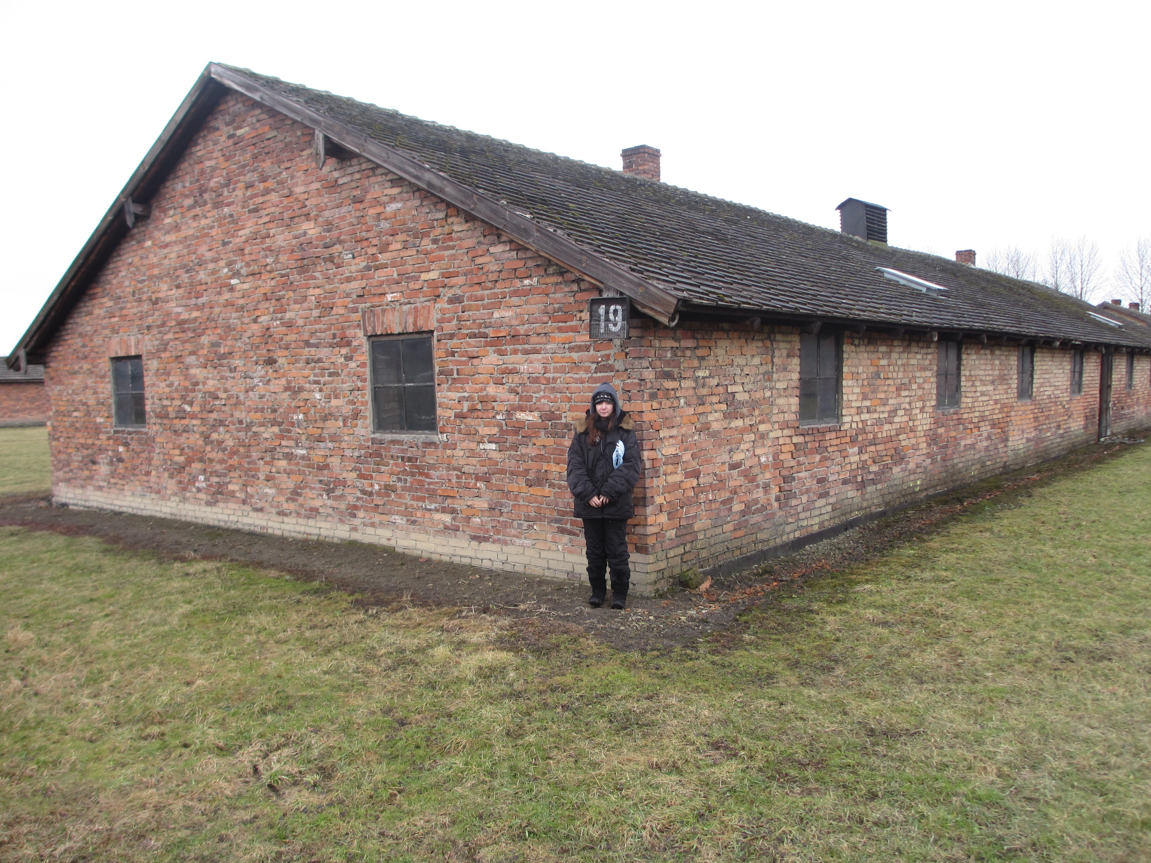 Elise Kolender, Jeffrey's daughter and Pincus' granddaughter, in front of another of the Auschwitz barracks - 2013